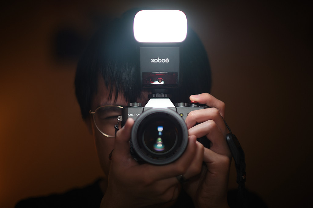 Self-portrait of me using my mirrorless camera with a dedicated flash on a mirror