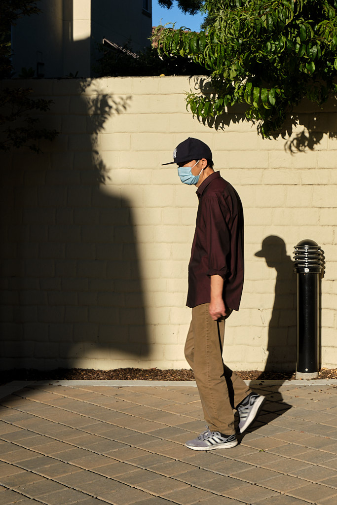 A man walking in front of his shadow