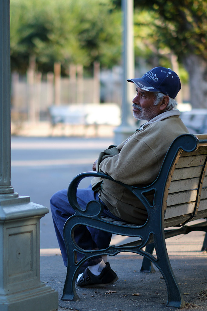 An older man sitting on a park bench with a wistful gaze